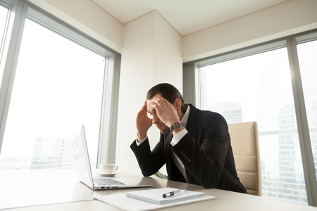 Stressed businessman at desk holding head in hands looking on pc laptop screen. Tired entrepreneur exhausted with too long work. Executive hard thinking about difficult problem, worried about result