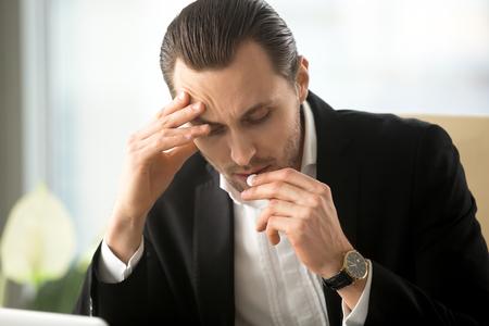 손으로 머리를 만지고 아픈 남자 강조 두통에서 흰색 라운드 알 약을 걸립니다. 사업가 감기의 첫 번째 증상을 막으려 고, 피로 완화, 마약 도움 스트레 스톡 콘텐츠