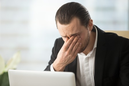Frustrated businessman feels pain in eyes because of eyesight overstrain after long computer work. Tired young man massaging eyes in front of laptop. Eyes fatigue, headache or dizziness at workplace 写真素材