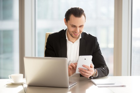 Happy businessman working on tablet at office desk. Successful entrepreneur communicates in internet, reading message, planning work with phablet. Executive manager using mobile app for online banking