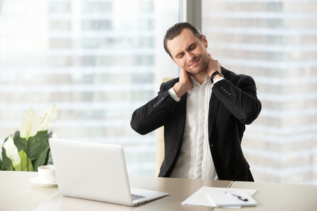 Businessman feeling pain in neck after sitting at desk. Tired man suffering of office syndrome after long hours work on computer. Entrepreneur massaging his tense neck muscles. Gymnastics at work