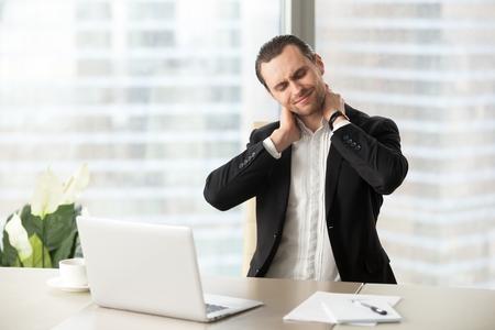Zakenman die pijn in hals na het zitten voelen bij bureau. Het vermoeide man lijden van bureausyndroom na urenlange werk op de computer. Ondernemer masseert zijn gespannen nekspieren. Turnen op het werk