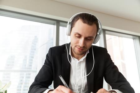 Mens die in hoofdtelefoons met pen bij het bureau schrijft. Ondernemer neemt deel aan online vergadering of conferentie, live stream, leren van vreemde talen. Zakenman luistert muziek tijdens het werken op kantoor Stockfoto