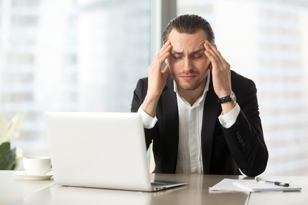 exhausting: Frustrated man squeezes temples with hands at desk in front of laptop. Tired businessman suffers from headache at workplace. Entrepreneur feels chronic fatigue, work stress because of business problem Stock Photo