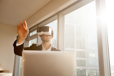 interacts: Businessman working in office with virtual reality glasses on head. Man using VR headset for editing project or document in augmented reality. Entrepreneur interacts with three-dimensional simulation