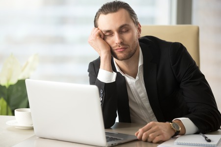 Young man dozing with head on hand while sitting at desk with laptop in office. Businessman sleeping at workplace in morning after weekend party day before. Tired male entrepreneur slumbers at work