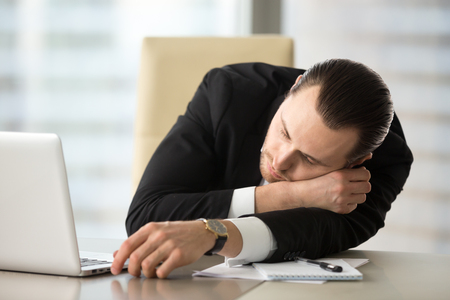 Man lying on work desk with hand placed under head. Businessman fall asleep at workplace after long sleep deprivation. Tired entrepreneur takes break and dozing in office. Chronic fatigue and overwork