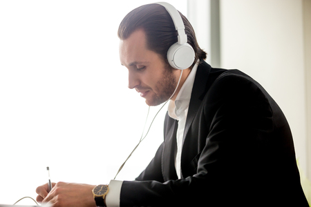 live stream listening: Businessman in headphones takes part in online meeting, conference. Young man learning foreign language, listening live stream. Entrepreneur works with enthusiasm and listens favorite music in office