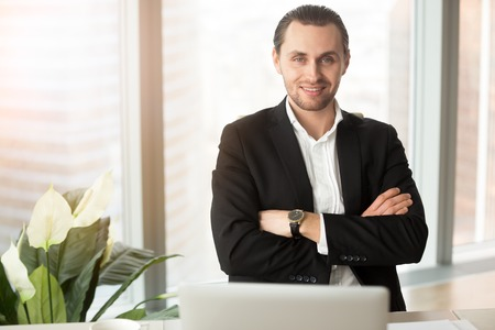 Portrait of young smiling guy in formal wear sitting at work desk in office with arms crossed and looking in camera. Confident businessman posing at workplace. Leadership, readiness to challenges