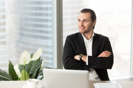 Young attractive businessman sitting at desk with crossed arms and dreamily looking away. Confident businessman imagines company great perspectives, dreaming about new achievements, enjoys success Stock Photo