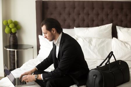 명품 아파트에 수하물을 침대에 앉아있는 동안 랩톱에서 작업하는 비즈니스 양복을 입고 심각한 남자. 외국인 파트너와 회의를 가기 전에 호텔 방에서 스톡 콘텐츠