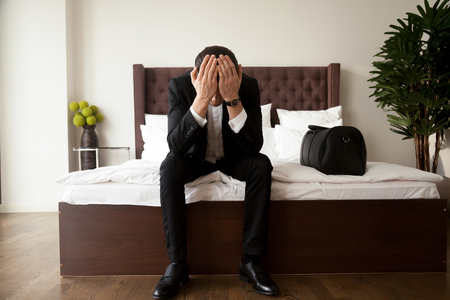 Upset stressed man in business suit sitting with head in hands on bed edge beside  handbag with belongings. Leaving home because of divorce, problems in relations or business, loss through loan debts