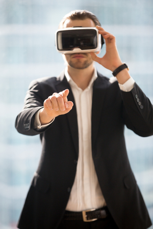 Businessman wearing virtual reality glasses, touching objects in digital world. Man in VR headset choosing, operating in virtual interface. Entrepreneur using electronic goggles for 3d visualization Stock Photo