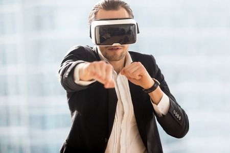 Man in business suit boxing with virtual reality glasses on head. Guy playing computer fighting game in VR headset. Digital entertainments, new technology, innovations in modern game industry concept Stock Photo