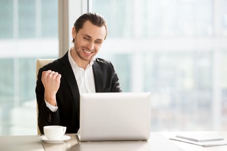 デスク ノート パソコンの画面上に見える幸せなビジネスマンは、拳の手をはい言います。若い起業家の会社と興奮、成長する証券取引所で株式価値