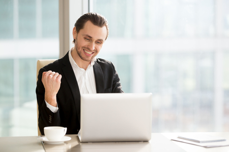 Happy businessman at desk looks on laptop screen, says yes with hand in fist. Young entrepreneur excited with company grow, jump of shares value on stock exchange. Guy celebrating success. Copy space
