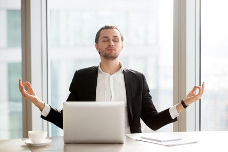 Relaxed young entrepreneur meditating at desk in front of laptop. Office worker doing yoga exercises at workplace. Successful businessman relieves stress with spiritual practices or autosuggestion Stock Photo
