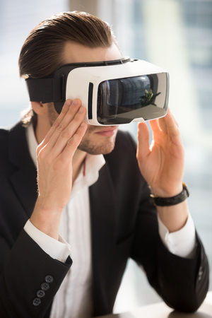simulator: Businessman wearing VR headset. Man in business suit adjusting virtual reality glasses on head. Modern digital entertainments, innovative technologies in business, realistic 360 degrees 3d experience Stock Photo