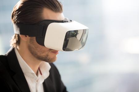 Sluit foto van virtuele werkelijkheidsglazen omhoog op bemant hoofd. Zakenman die in VR-hoofdtelefoon kijkt. Werk in augmented reality, digitaal amusement, virtueel gamen, cyberspace-belevingsconcepten. Ruimte kopiëren Stockfoto