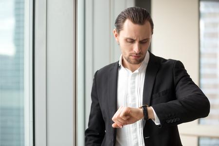 Bezige zakenman die polshorloge bekijkt terwijl het haasten zich op vergadering in bureau. De jonge mens in pak controleert tijd verlaten tot eind van het werkdag. Ondernemer bezorgd, tijdgebrek bij belangrijke werktaken
