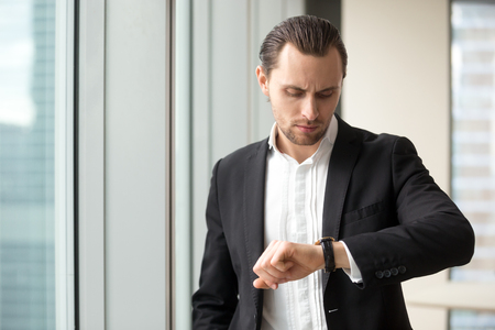 Busy businessman looking at wristwatch while hurrying on meeting in office. Young man in business suit checks time left to end of work day. Entrepreneur worried, lack of time on important work tasks
