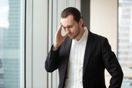 Man in formal wear standing with eyes closed touching temple because of head pain, dizziness. Businessman feels headache, recalling bad memories. Entrepreneur suffers from fatigue, overwork in office Stock fotó