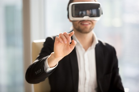 Entrepreneur in VR headset interacts with application virtual interface, pressing invisible buttons or selects menu items. Businessman works in office augmented reality. Cyberspace experience concept Banco de Imagens