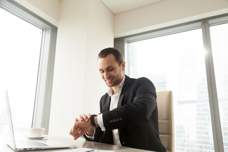 Successful businessman looking at wristwatch while sitting at desk with laptop in office. Company leader checks time remaining to start online conference, intends to go on important meeting or lunch