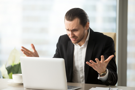 Upset shocked businessman at office table looks at laptop screen with surprised confused expression, lost finance data. Emotional office worker don t understand cause of computer problem at workplace Stock Photo