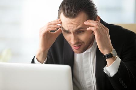 Zakenman geschokt met val van bedrijfsvoorraden. Benadrukt ondernemer met hoofd in handen op zoek op laptop scherm met paniek. Jonge man in wanhoop vanwege slecht nieuws, opzegtermijn, schuldenlast Stockfoto - 79165968
