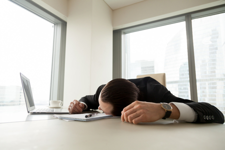 Exhausted businessman lying on his desk with laptop and documents. Tired office worker sleeping at workplace. Entrepreneur feeling weakness because of stress, gets depressed. Difficult work concept