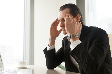 exhausting: Frustrated man with closed eyes massaging temples at desk in office. Businessman suffers from migraine headache caused by high blood pressure. Tired entrepreneur feels nervous tension, stress at work Stock Photo