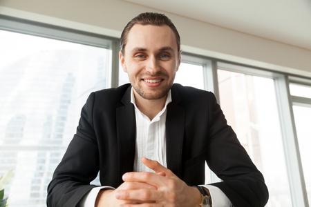 Portret van jonge aantrekkelijke man in pak zittend aan een bureau op zoek in de camera met een glimlach. Zakenman voelt positieve emoties tijdens onderhandelingen met partners. Baas op interview met sollicitanten Stockfoto