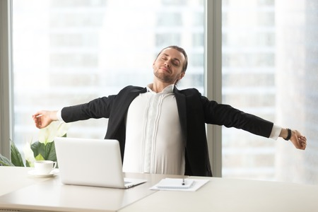 Businessman stretching out at desk with laptop. Office worker doing relaxing exercises at workplace to relieve physical fatigue Manager make deep breath of fresh air, relaxed after finishing work