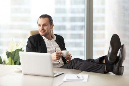 Confident businessman with legs on desk relaxing with cup of coffee during break at work. Company leader enjoys success in business, dreaming about career perspectives, imagines future with pleasure Stock Photo