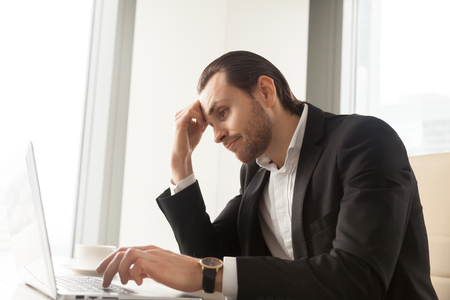 skepticism: Young businessman at desk tired from routine laptop work. Entrepreneur boring at workplace, sick of monotonous work. Office worker procrastinates while trying complete dull report. Lack of motivation Stock Photo