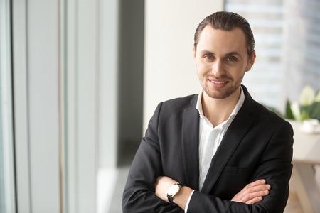 両手を交差し、笑顔でカメラで見て立っている成功した会社の若いリーダーの肖像画。起業家のオフィスのインテリアでポーズをとる彼自身の能力