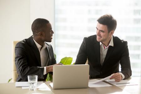 두 명의 성취 된 multiracial 기업인 사무실 책상, 실내에서 쾌적 한 재미있는 대화를하는 멀티 인종 비즈니스 그룹 아이디어를 논의 새로운 비즈니스 프