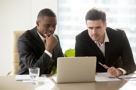 プレゼンテーション、思いやりに焦点を当てて、ノート パソコンの画面を見て正式な摩耗で会議に 2 人のビジネスマンはタスクに集中して問題を解 写真素材