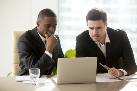 Two businessmen on meeting in formal wear looking at laptop screen, focused on presentation, thoughtful concentrated on task, trying to solve problem, analyzing market, considering business offer