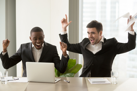 Two happy businessmen in suits raising hands near laptop, multicultural business group celebrate victory, stock trading success, impressive achievements, great luck, win important contract, we did it
