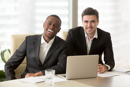 Two cheerful businessmen wearing suits sit at the desk, looking at camera, friendly entrepreneurs ready for collaboration, running successful company together, multiracial business partners portrait
