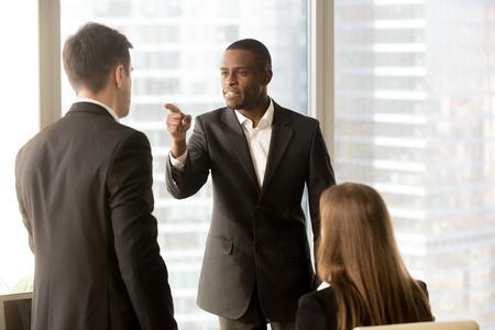 De boze Afrikaans-Amerikaanse zakenman bedreigt collega, conflict tussen mannelijke arbeiders op het werk, intimidatie en onderscheid, de zwarte werkgever beschuldigt witte werknemer verantwoordelijk voor mislukking, uw fout