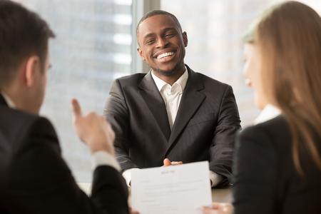 L'employeur montre le pouce vers le candidat noir réussi à l'entrevue, le patron de l'entreprise satisfait des résultats du travail des employés africains, l'initié a obtenu un fonds d'investissement pour l'idée d'entreprise, un bon travail Banque d'images - 80154173