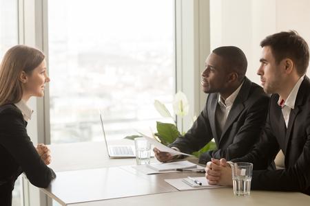Zijaanzicht van vrouwelijke sollicitant die zichzelf introduceert tijdens sollicitatiegesprek, praten over werkervaring, multiraciale recruiters hr managers interviewen luisteren naar kandidaat, rekening houdend met cv CV Stockfoto