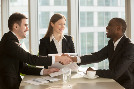 Happy smiling black and white businessmen handshaking after signing contract at multi-ethnic meeting with businesswoman, multiracial partners shaking hands, sealing closing deal with satisfied client Stock Photo
