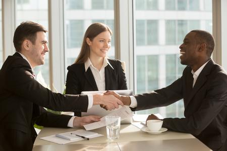 Het gelukkige het glimlachen zwart-witte zakenliedenhandenschudden na het ondertekenen van contract bij multi-etnische vergadering met onderneemster, multiraciale partners die handen schudden, verzegelende sluitende overeenkomst met tevreden cliënt