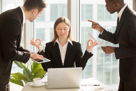Mooie zakenvrouw mediteren op de werkplek, het negeren van werk, niet luisteren naar vervelende klanten of stoorde collega's met haar praten, zittend aan een bureau met gesloten ogen, blijf kalm, geen stress