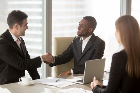 Twee vrolijke zakenlieden handshaking op formele vergadering, beginnen met afwerking onderhandelingen, Afrikaanse ondernemer dragen zwart pak wit overhemd en Kaukasische partner handen schudden, maken van winstgevende deal