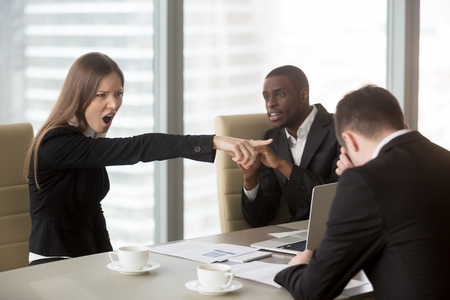 Angry female furious boss scolding employee at mixed-race team meeting, firing dismissing depressed office worker for failure, bad work results, being ineffective, pointing finger, its your fault Stockfoto